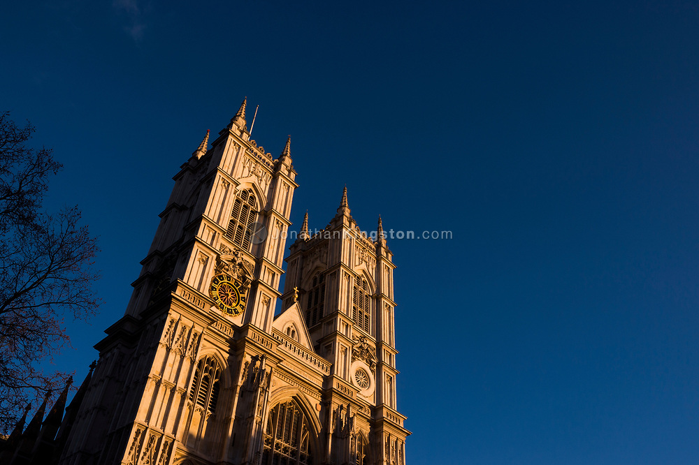 Low angle view of Westminster Abbey at sunset against a deep blue sky in London, England.