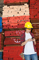 Asian female industrial worker using cell phone with stacked wooden planks in background