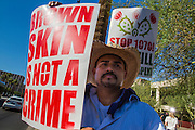 25 JUNE 2012 - PHOENIX, AZ: A protester stands in front of the Immigration and Customs Enforcement (ICE) offices in central Phoenix Monday. About 100 immigration supporters held a protest against ICE and continued deportations by the Obama administration. Protesters also celebrated the US Supreme Court decision to overturn most of SB1070, Arizona's tough anti-immigration law.      PHOTO BY JACK KURTZ