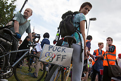 "© licensed to London News Pictures. London, UK 28/07/2012. A small placard attached to a bike reading ""Puck off"" with Olympic logo as anti-Olympics protesters gathering in Mile End Park to march to Victoria Park in order to protest against the greed of the Olympic sponsors. Photo credit: Tolga Akmen/LNP"