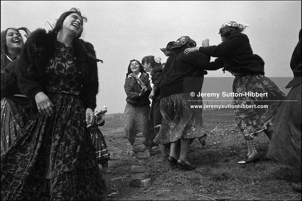"""PLAYING  THE BALL GAME """"CASTEL"""" (CASTLE). SINTESTI, ROMANIA. MAY 1997. Kalderash Roma women from the camp of Sintesti, near Bucharest, play a ball game called 'Castle' in the fields near their camp, as part of their Romanian Orthodox easter celebrations. Easter is the most important date in their calendar."""