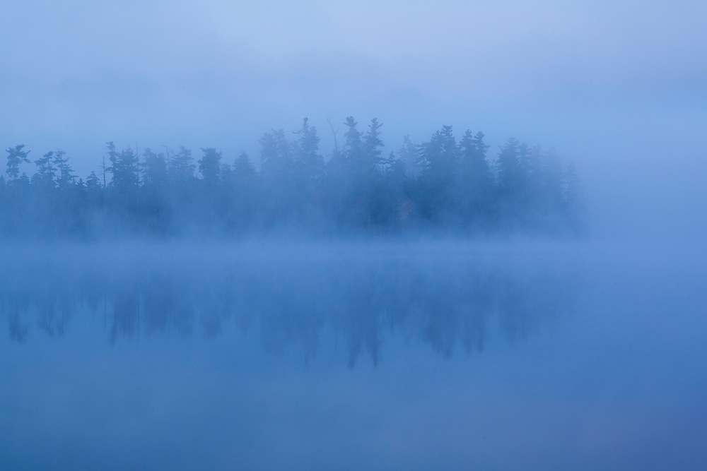 mist rises off a pond in the adirondacks at dawn