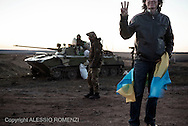 Ukraine, Myrne: A pro Ukraine supporter shows the Ukrainian flag and flashes the victory sign in front of Ukrainian soldiers standing guard at the entrance of a temporary military camp set in the countryside of Myrne, an Ukrainian village located some 40 Km from the border with Russia on March 19, 2014. Ukrainian troops, armoured vehicles and tanks have been seen on their way to the eastern border with Russia. During the journey al least two convoys have been stopped by pro Russia protesters that prevented them to reach the border zone. ALESSIO ROMENZI