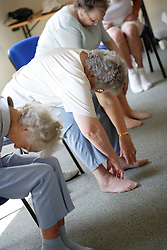 Group of older women doing stretching exercises at a keep fit class,