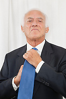Portrait of confident elderly businessman adjusting his necktie