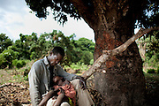 A tired father waits outside the local health clinic to open in the village of NDOMETE... with his son who are severely sick with Malaria. He walked 15 km. to get to the clinic to help his son.The central African rep. has some of the world's worst child welfare indicators. The infant mortality rate is 112, and out of 1,000 children born in CAR, 171 will die before reaching the age of five. The five main child killers in CAR are malaria, diarrhoea, acute respiratory infections, malnutrition and measles – all preventable diseases. The Accelerated Child Survival and Development Strategy UNICEF is implementing aims to reach every newborn and child in every district with a set of priority interventions. Evidence shows that there are a number of known and affordable interventions that if implemented fully could prevent 63 per cent of current childhood mortality.