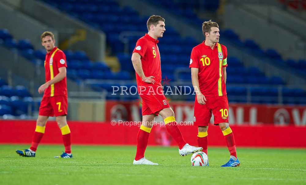 CARDIFF, WALES - Tuesday, September 10, 2013: Wales' Sam Vokes and captain Aaron Ramsey look dejected after Serbia score the third goal during the 2014 FIFA World Cup Brazil Qualifying Group A match at the Cardiff CIty Stadium. (Pic by David Rawcliffe/Propaganda)