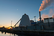 Steam rises from the Nippon paper plant at sunset, along the shore of the Strait of Juan de Fuca and Ediz Hook in Port Angeles.