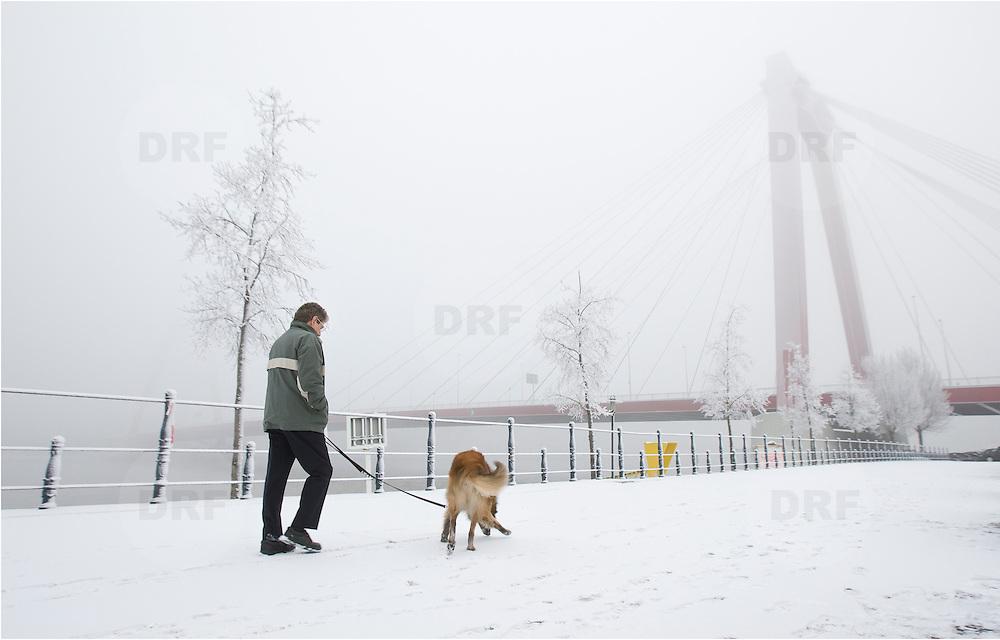 Nederland Rotterdam 21 december 2007 ..Man laat hond uit op een besneeuwd Noordereilandop de achtergrond de Willemsbrug...Foto David Rozing