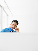 Portrait of smiling young businessman using cell phone at office