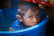 13 APRIL 2013 - BANGKOK, THAILAND:   A Thai boy hides in a barrel of water during Songkran on Soi Nana, off of Sukhumvit Road in Bangkok. Songkran is celebrated in Thailand as the traditional New Year's Day from 13 to 16 April. The date of the festival was originally set by astrological calculation, but it is now fixed. If the days fall on a weekend, the missed days are taken on the weekdays immediately following. Songkran is in the hottest time of the year in Thailand, at the end of the dry season and provides an excuse for people to cool off in friendly water fights that take place throughout the country. Songkran has been a national holiday since 1940, when Thailand moved the first day of the year to January 1.  PHOTO BY JACK KURTZ