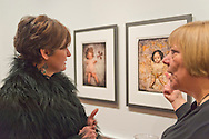 Huntington, New York, U.S. - March 1, 2014 - At right, artist LOIS YOUMANS discusses with a visitor the humorous artwork in Youmans' exhibit 'Vitreous Humor – A Collection of Absurd Images,' at the Opening Reception '3 Wild & Crazy Artists' at FotoFoto Gallery. The images are a combination of photographs of dolls and vintage medical illustrations.