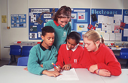 Multiracial group of secondary school pupils working together on science project,