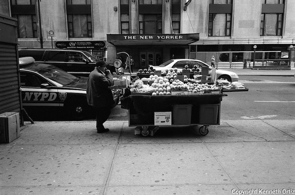 A fruit vendor on 34th Street between 8th & 9th avenues, in Manhattan across the street from the New Yorker Hotel.