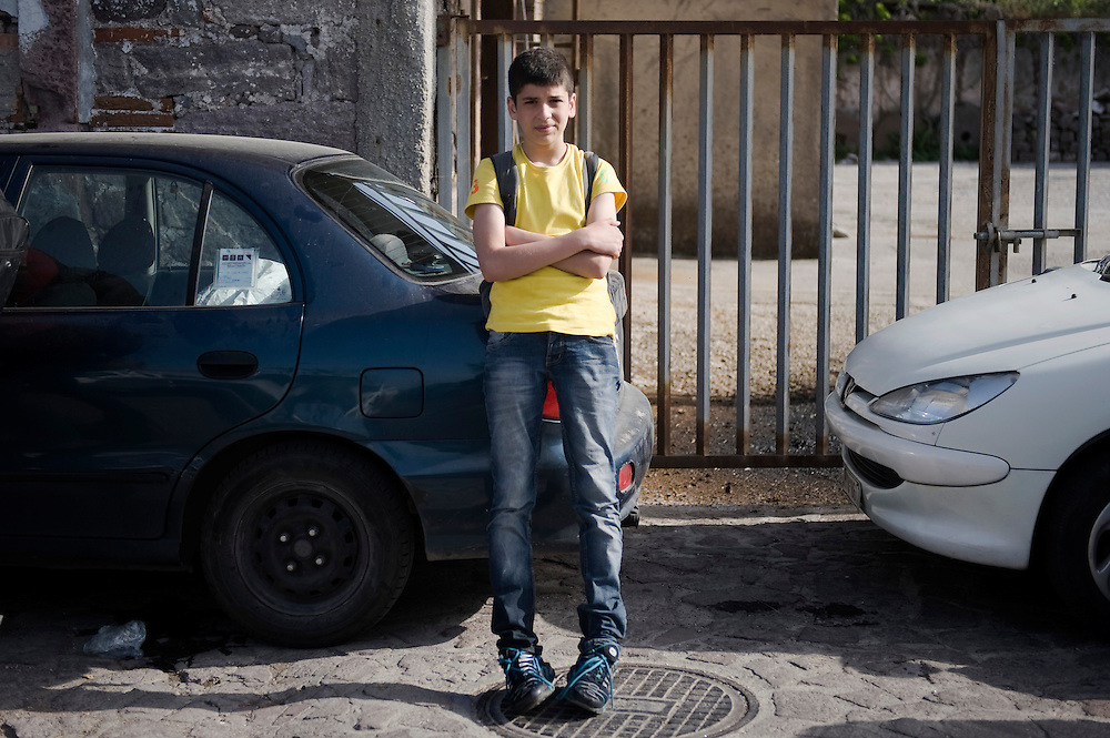 15 year old Sharaf from Damascus standing by parked cars in Skala Sykaminias after his arrival in Lesbos island. He has been traveling on his own since his family has been killed in the Syrian civil war. <br /> Everyday hundreds of refugees, mainly from Syria and Afghanistan, are crossing in small overcrowded inflatable boats the 6 mile channel from the Turkish coast to the island of Lesbos in Greece.