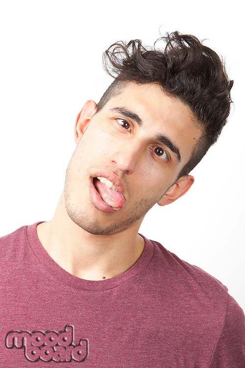 Portrait of young Middle Eastern man making funny faces over white background