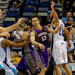 February 2, 2012; New Orleans, LA, USA; Phoenix Suns point guard Steve Nash (13) passes away from defensive pressure by New Orleans Hornets power forward Gustavo Ayon (15) and point guard Jarrett Jack (2) during the second quarter of a game at the New Orleans Arena.   Mandatory Credit: Derick E. Hingle-US PRESSWIRE