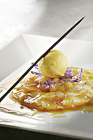 Broiled pineapple carpaccio on a whiet plate, Vanilla saffron ice cream on top
