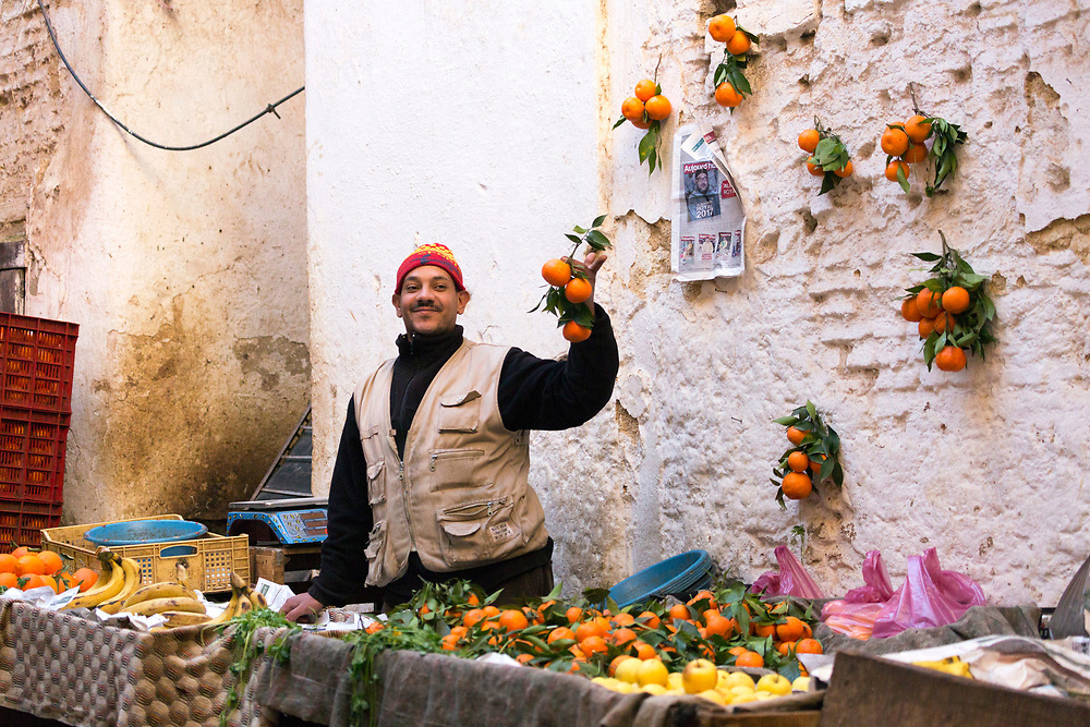 Fez, Morocco - 3rd FEBRUARY 2018 - Fruit and veg vendor selling oranges at his market stall in the old Fez Medina, Middle Atlas Mountains, Morocco.