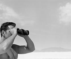 Shirtless man looking through binoculars in White Sands New Mexico