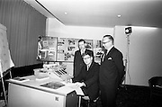 22/05/1964<br /> 05/22/1964<br /> 22 May 1964<br /> Contract signed for new Burroughs Accounting Machine. Mr Kelvin J. Smythe (centre), Managing Director of E.C. Handcock Ltd. signing an order for a Burroughs Series E Direct Accounting Computer System at Jury's Hotel, Dublin. This was the second Irish Company to order one since its release that month. Included in the image are: Mr J. Geddes, Manager Burroughs Machines Ltd., (right) and Mr T. Barrett, Systems Consultant.