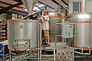 Brian Owens, brewer at O'Fallon Brewery, puts the lid back on the mash/lauter tun.