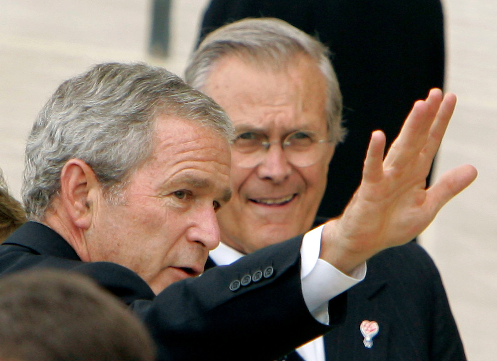 US President George W. Bush waves the families of victims as Secretary of Defense Donald Rumsfeld watches during ceremonies marking the fifth anniversary of the September 11 attacks on America at the Pentagon in Washington, September 11, 2006.   REUTERS/Joshua Roberts   (UNITED STATES)