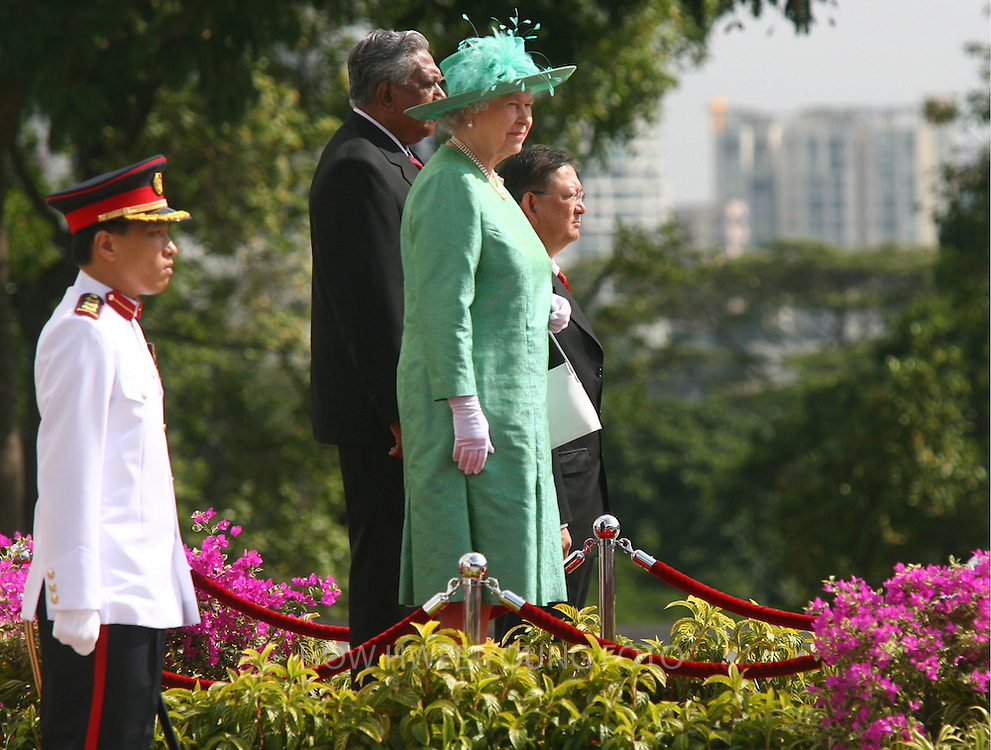epa00669750 Queen Elizabeth II (C) of the United Kingdom and Singapore's President S. R. Nathan (behind) stand at the welcome ceremony at the Istana in Singapore on Friday 17 March 2006. The Queen is in the city state for a three-day state visit after officiating the Commonwealth games in Australia.  EPA/HOW HWEE YOUNG