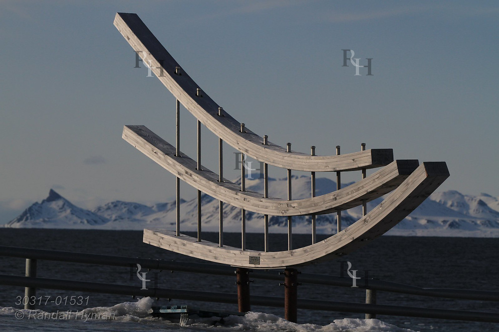 Wooden sculpture at the international science village of Ny-Alesund on Spitsbergen island overlooks fjord of Kongsfjorden; Svalbard, Norway.