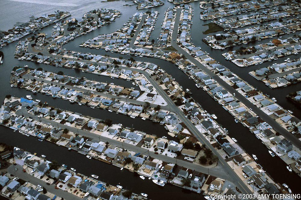 STAFFORD, NJ - SEPTEMBER 21: An aerial view of the Beach Haven West housing development next to protected wetlands September 21, 2003 in Stafford, New Jersey. The site that Beach Haven West is located on was known as Remson Meadows along the Manahawkin Bayfront. The Shapiro Brothers bought the marshes in 1950 to develop the area with summer vacation homes. However, the intended development was never fully completed, due to a lack of permits and increasing pressure from the EPA. Eventually the Wetlands Protection Act of 1970 kept the community from expanding further. The Jersey Shore, a 127 mile stretch of coastline known for its variety of beaches, boardwalks, small towns, natural beauty and summer crowds, has been a popular summer destination for over a century. (Photo By Amy Toensing)
