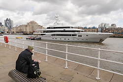© Licensed to London News Pictures. 29/03/2018. London, UK. A man looks at the 220ft custom luxury superyacht, 'Global' moored at Butlers Wharf near Tower Bridge during a London visit. Previously named, Kismet during her last central London visit, she underwent a refit which saw her moved up 51 places in Boat International's list of top 200 largest super yachts in the world, boasting numerous luxuries such as a helipad, cinema and jacuzzi. Believed to be owned by Fulham Football Club chairman, Shahid Khan, Global can be chartered for an estimated £1m per week. Powered by 2 Caterpillar (3512 B) 2,038hp diesel engines and propelled by her twin screws propellers, Global is capable of a top speed of 15.5 knots, and comfortably cruises at 14 knots. . Photo credit: Vickie Flores/LNP