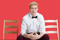 Portrait of a handsome young man in formal wear sitting on chair over red background