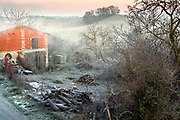 early morning wintry rural landscape with a pile of firewood France