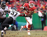 Kansas City Chiefs running back Larry Johnson (27) brakes away for Jacksonville safety Deon Grant (37) for a 48-yard run in the second quarter at Arrowhead Stadium in Kansas City, Missouri, December 31, 2006.  The Chiefs beat the Jaguars 35-30.<br />