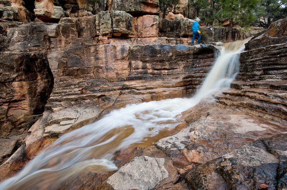 040110        Brian Leddy.A woman watches a waterfall in Milk Ranch Canyon in the Zuni Mountains.