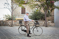 ACCIAROLI (POLLICA), ITALY - 5 OCTOBER 2016: Mr. Monga (88 years old) poses for a portait on his bicycle in the historical centre of Acciaroli, a hamlet in the municipality of Pollica, Italy, on October 5th 2016.<br /> <br /> To understand how people can live longer throughout the world, researchers at University of California, San Diego School of Medicine have teamed up with colleagues at University of Rome La Sapienza to study a group of 300 citizens, all over 100 years old, living in Acciaroli (Pollica), a remote Italian village nestled between the ocean and mountains in Cilento, southern Italy.<br /> <br /> About 1-in-60 of the area's inhabitants are older than 90, according to the researchers. Such a concentration rivals that of other so-called blue zones, like Sardinia and Okinawa, which have unusually large percentages of very old people. In the 2010 census, about 1-in-163 Americans were 90 or older.