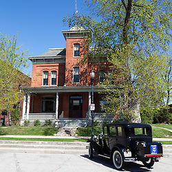 """Old Sheriff's House and Lake County jail in Crown Point Indiana with a Ford Model A antique car parked in front. In 1934 John Dillinger escaped from the Lake County jail in this building. In 2008 Universal Studios filmed parts of the movie Public Enemies with Johnny Depp. The jail is open to the public for tours and goes past Dillinger's cell and also where filming was done. Crown Point is located in Northwest Indiana with a population of over 37,000. Crown Point and Lake County are about 50 miles from Chicago and are considered part of the """"Chicagoland"""" area. Crown Point has a traditional small town America feel with a main street consisting of the old Lake County Courthouse surrounded by numerous small businesses, known as """"the square"""", including a theater, ice cream shop, antique stores, and restaurants."""