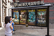 A mother and son view movie posters in Xintiandi Plaza shopping district Shanghai, China