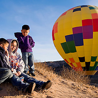 120112       Cable Hoover<br /> <br /> La'Rhonda Tom sits with her sons Elijah Trickey, left, and Noah Trickey to watch the balloons as they float among the cliffs during the Red Rock Balloon Rally at Red Rock Park Saturday.