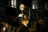 A deacon carries a fan as another holds aloft a copy of the holy gospel during Sunday liturgy services at the Refectory Church of Sts. Anthony and Theodosius at the Pechersk Lavra on Sunday, October 7, 2018 in Kyiv, Ukraine.