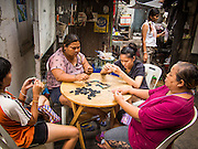 "19 AUGUST 2013 - BANGKOK, THAILAND: Thai women gamble by playing dominos at a neighborhood gambling center in the ""Ban Bat"" neighborhood of Bangkok, Thailand. Even though gambling is technically illegal in Thailand, Thais like to gamble and informal games of chance are common in Bangkok.      PHOTO BY JACK KURTZ"