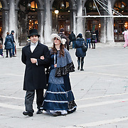 VENICE, ITALY - FEBRUARY 20:  A couple wearing Carnival costumes and masks walks in St Mark Square on February 20, 2011 in Venice, Italy. The Venice Carnival, one of the largest and most important in Italy, attracts thousands of people from around the world each year. The  theme for this year's carnival is Ottocento amd Sissi, a nineteenth century evocation, and will run from February 19 till March 8.