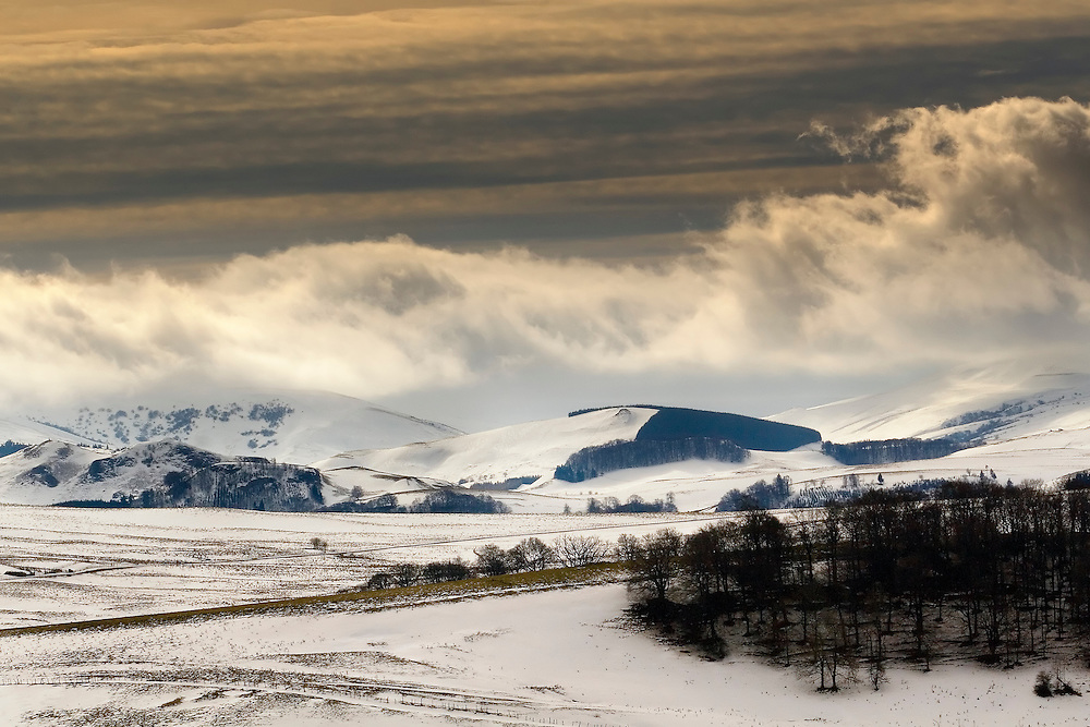 Hills covered with snow and clouds in sunset light. Auvergne, France