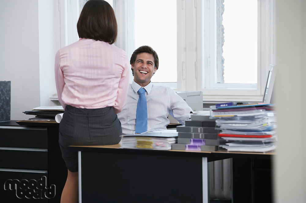 Business man and woman talking in office smiling