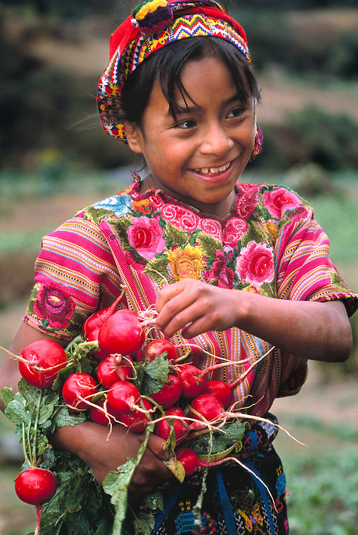 South America, Guatemala, girl in traditional clothing harvesting radishes in field