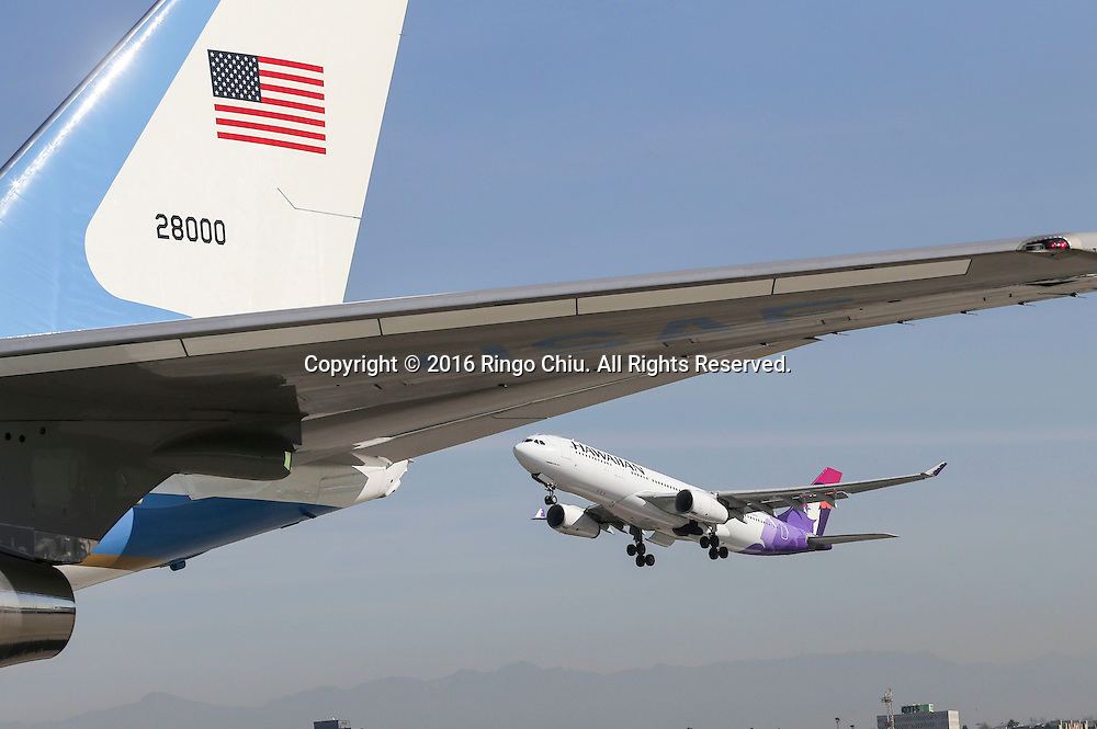 A Hawaiian Airlines aircraft flies past Air Force One sitting on the tarmac before President Barack Obama boarding at Los Angeles International Airport in Los Angeles, Friday, Feb 12, 2016.(Photo by Ringo Chiu/PHOTOFORMULA.com)<br /> <br /> Usage Notes: This content is intended for editorial use only. For other uses, additional clearances may be required.