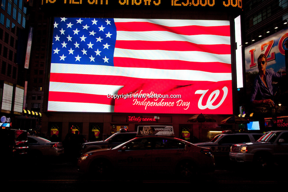 New york times square , 42nd street at sunset.  american flag on a bilboard , yellow cabs ,