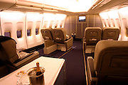 on board a commercial flight First class with a bottle of Champagne
