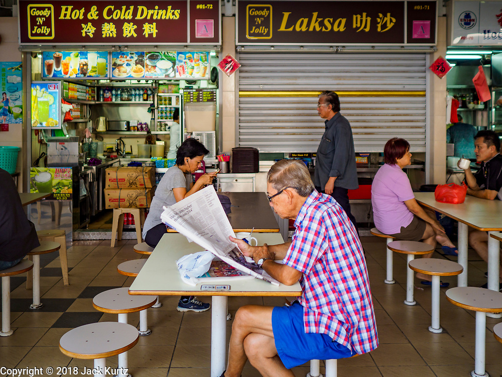 """11 DECEMBER 2018 - SINGAPORE:  A man reads his newspaper in a """"hawker"""" court at the Haig Road Market and Food Centre in the Geylang neighborhood. The Geylang area of Singapore, between the Central Business District and Changi Airport, was originally coconut plantations and Malay villages. During Singapore's boom the coconut plantations and other farms were pushed out and now the area is a working class community of Malay, Indian and Chinese people. In the 2000s, developers started gentrifying Geylang and new housing estate developments were built.     PHOTO BY JACK KURTZ"""