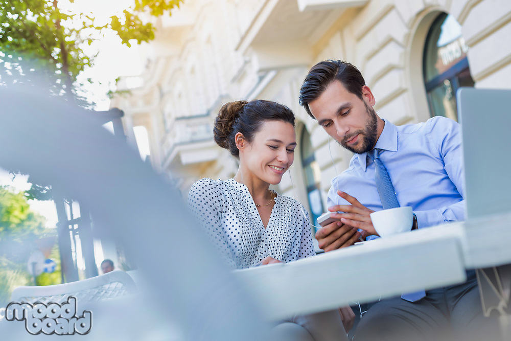 Businessman showing smartphone to businesswoman while having coffee during office break